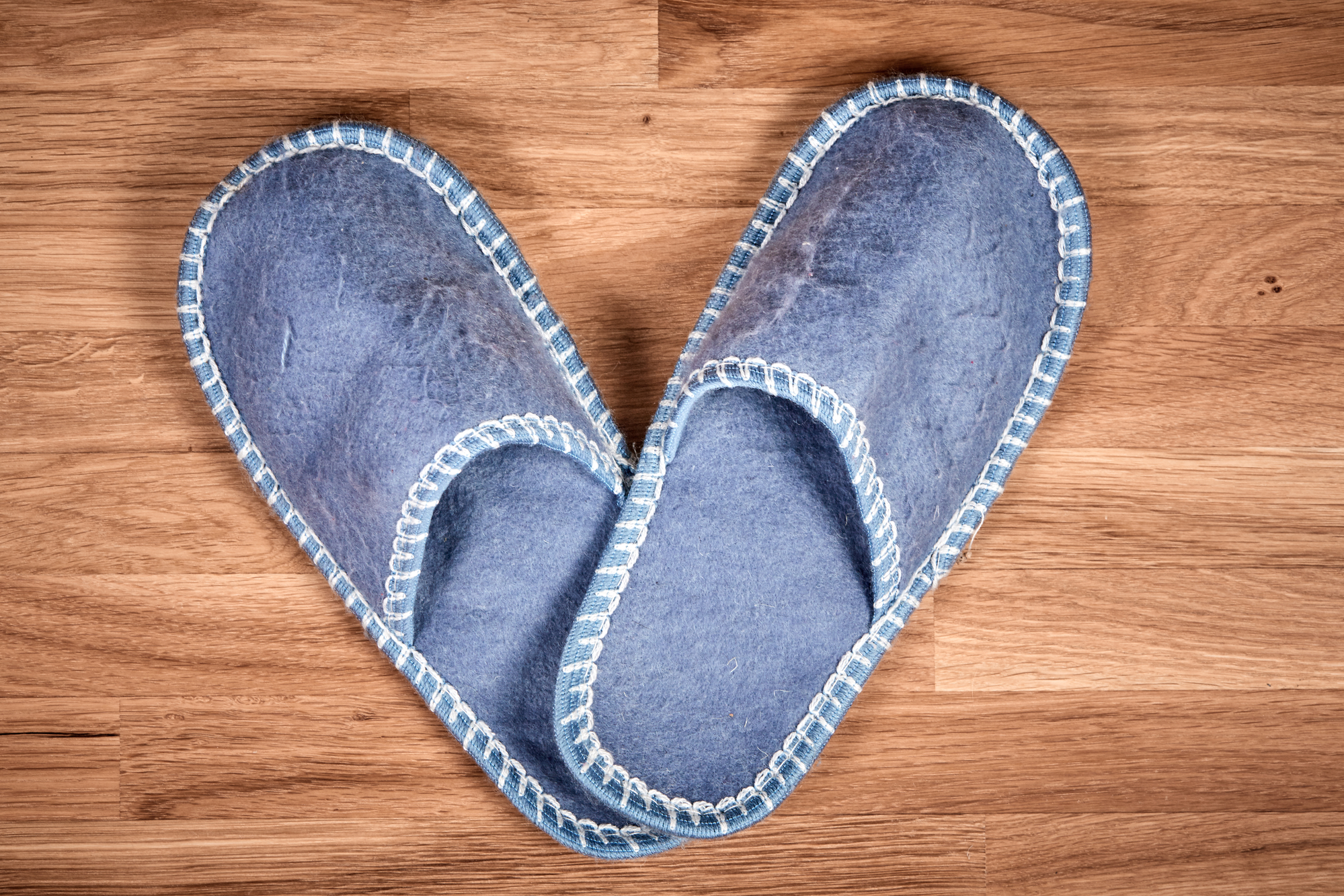 Blue household slippers on a brown woodenoak  floor